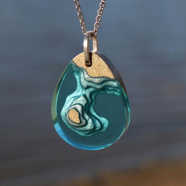 Peninsula pendant with dark coastal background