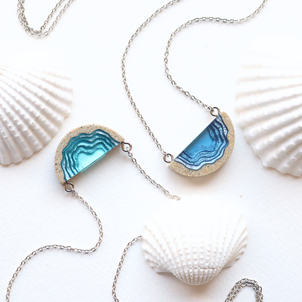 Two dainty beach sand and blue resin necklaces with grey background