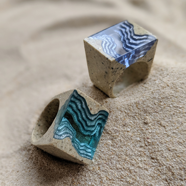 Two rift blue resin statement rings in beach sand